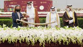 His Highness The Amir Sheikh Tamim bin Hamad al-Thani presents the trainer's trophy to Julian Smart
